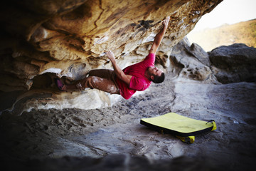 A man free climbing on the overhang of a rock face, with minimum equipment.