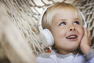 A young boy lying in a hammock wearing music headphones.
