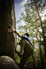 Bouldering, a climber climbing steep cliffs  in the woods near Essex, Massachusetts, free climbing.