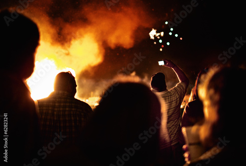 Silhouettes of people around a large bonfire.