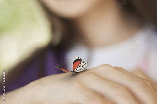 A child examining a butterfly, which has landed on her hand.