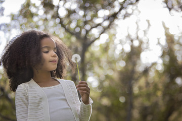 A young girl holding and blowing a dandelion seed head clock.