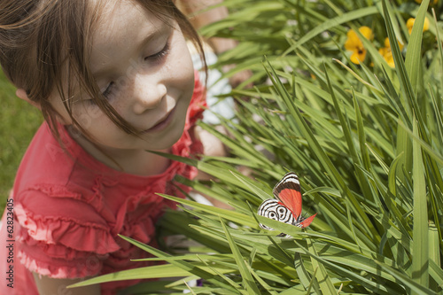 A young girl looking at a colourful butterfly in the grass.