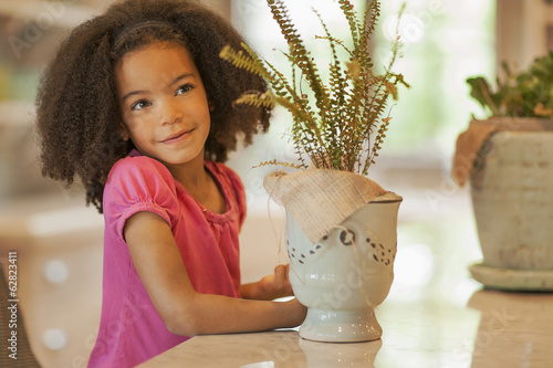 A child sitting at a table, with pots and plants.
