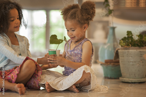 Two young girls sitting on a tabletop, holding a pot with a seedling and leaf shoot.