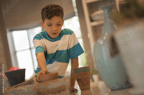 A boy planting out seedlings in clay pots, sitting on a table top.