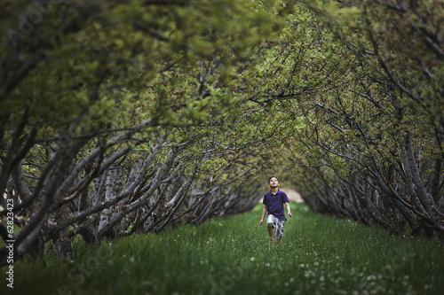 A child running along a natural woodland tunnel with tree branches forming an arch.