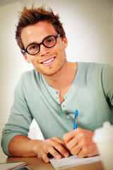 Portrait of young man filling in application form