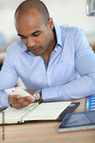 Young businessman recording meeting time in agenda