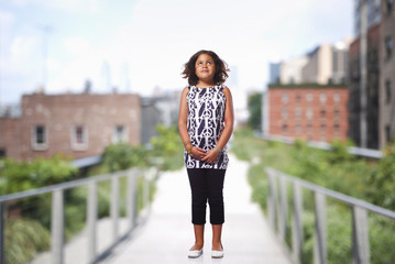 A child standing on a bridge in a green space in front of city buildings.
