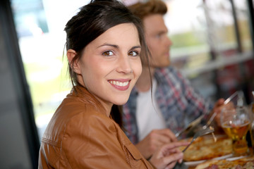 Smiling brunette girl having pizza for lunch