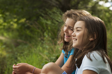 Two children, girls sitting side by side, laughing in the fresh air.