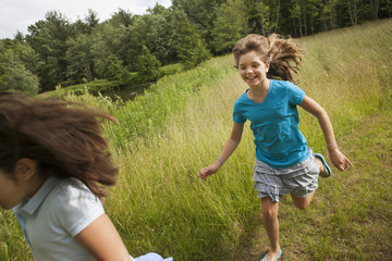 Two children, girls playing chase and running along a path.