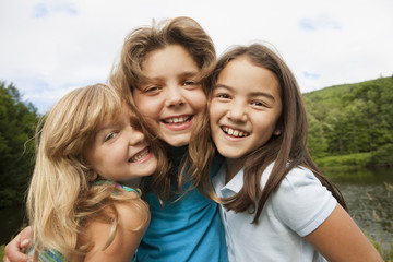 Three young girls, friends side by side, posing for a photograph in the open air.