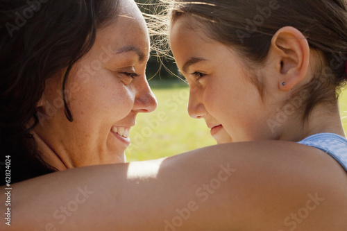 A mother and daughter embracing, an adult and child.