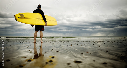 A middle aged man surfing in New England on Rockport Beach.