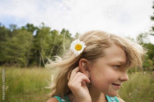 A young girl in the open air, with a daisy like flower behind her ear.