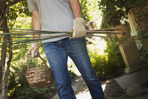 Organic Farming. A woman wearing work gloves, carrying basket and tools.