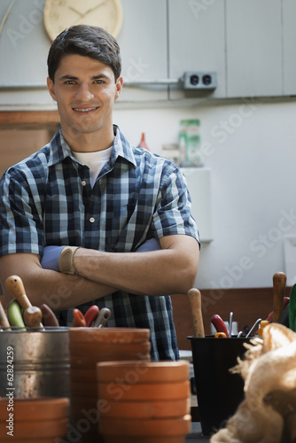 Organic Farm. A young man in a potting shed by work bench.