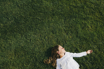 Nine year old girl smiling and resting on field of lush, green grass