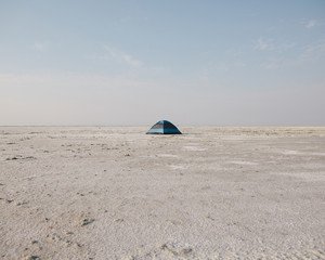 A blue tent on Bonneville Salt Flats at dusk.