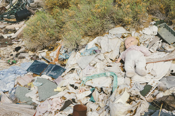 A heap of garbage and discarded items. Rubbish, paper and a children's doll.