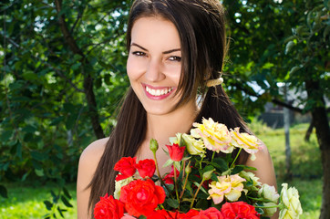 Beautiful woman in the garden with red and yellow roses,flowers.