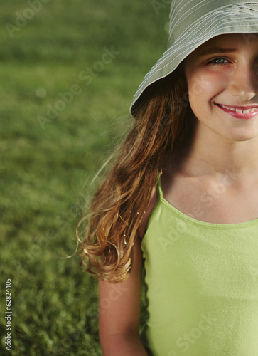 Portrait of smiling nine year old girl, field of grass in background