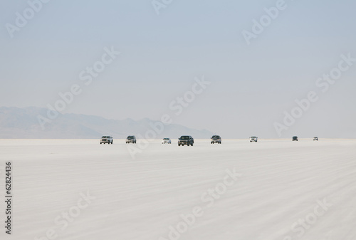 Cars driving on Bonneville Salt Flats during Speed Week. Dusk.