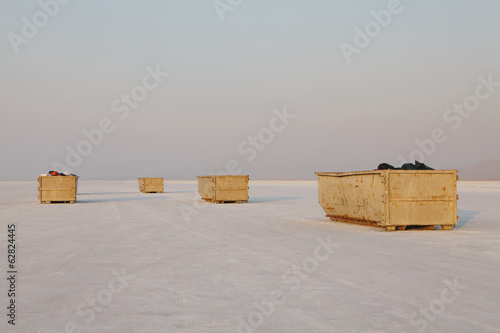 Large yellow garbage containers on Bonneville Salt Flats, dusk, near Wendover.