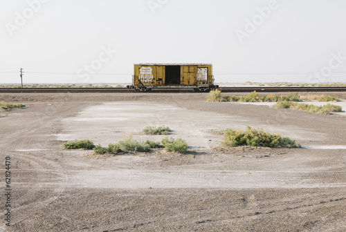 An empty box car or freight wagon on the train tracks in the desert.