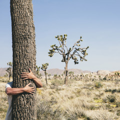 Man hugging a Joshua Tree in Joshua Tree national park.