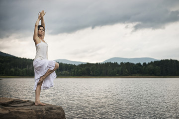 A woman dancing gracefully in the open air, standing on a rock by a lake near Woodstock, New York State, USA