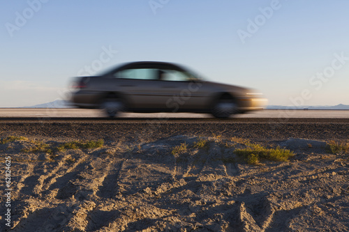 A saloon car driving through the desert at dusk.