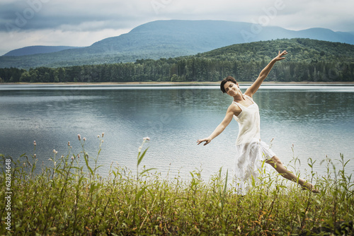 A woman dancing gracefully in the open air along the lake shore near Woodstock, New York State, USA