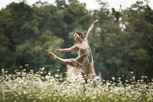 A woman dancing in a field of wild flowers.