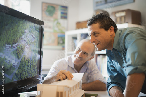 Two architects working on a green construction project, using computer technology. Scale model of a building. Computer design.