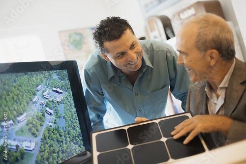 Two men in an architecture office. Working on a green construction project, sitting by a screen. A man holding a tile sample.