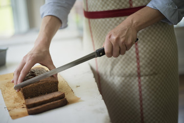 A woman cutting a baked chocolate cake.