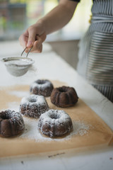 A woman dusting fresh made chocolate buns with icing sugar.