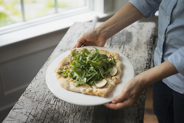 A person holding a plate with fresh salad and ingredients on baked bread.