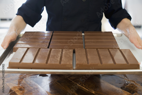 Organic Chocolate Manufacturing. A person holding a tray of processed chocolate slabs.