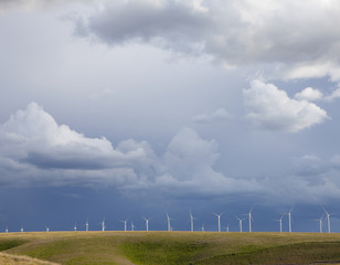 A line of wind turbines on a ridge, against a stormy sky.