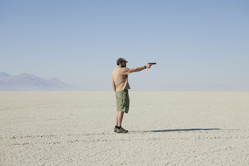 Man aiming hand gun, standing in vast, barren desert