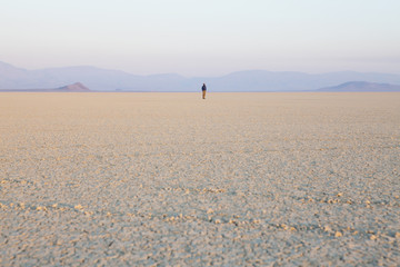 The figure of a man in the empty desert landscape of Black Rock desert, Nevada.
