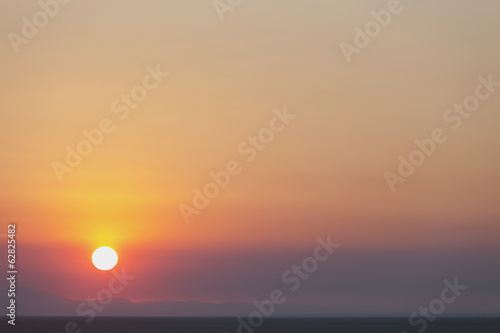 The rising sun over flat desert landscape at dawn in Nevada.