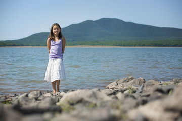 A young girl in a white skirt and purple top. Standing on the shore of a lake.
