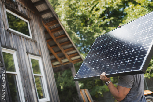 A man carrying a solar panel on a green construction site, working on a green building project.