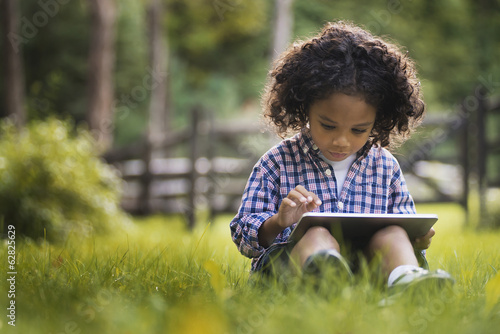 A small boy sitting on the grass using a tablet computer.