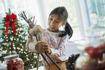 A young girl assembling a twig figure of a reindeer, making Christmas decorations.